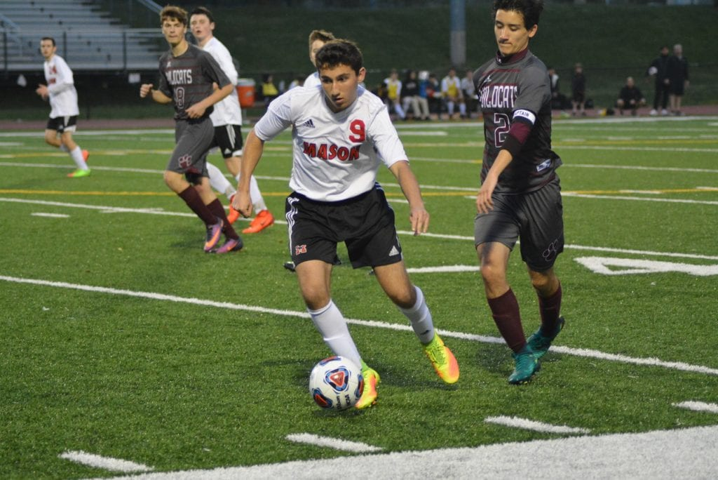 EVADING A DEFENDER is junior forward Peter Scardino. Scardino scored one of Mason's eight goals against Warren County on Tuesday night (Photo: Carol Sly)