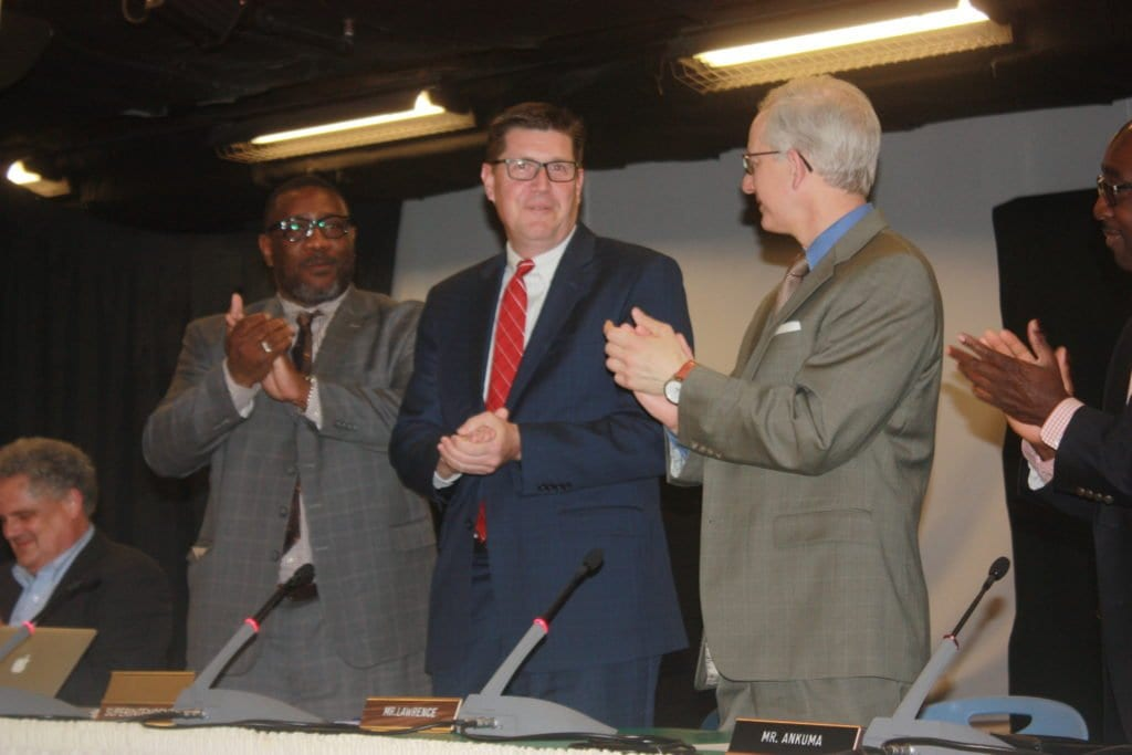 DR. PETER NOONAN (center) is flanked by Falls Church School Board chair Lawrence Webb (left) and board member John Lawrence while enjoying a rousing round of applause at tonight's formal vote and signing on at the City schools' ninth superintendent. (Photo: News-Press)