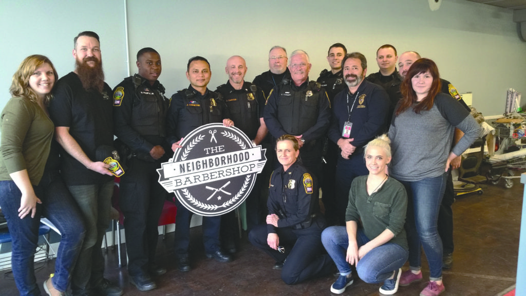"""CITY OF FALLS CHURCH POLICE with Neighborhood Barbershop staff pose before the """"Police Shave Off"""" after the department's Beards for Buddy campaign in November. (Courtesy Photo)"""