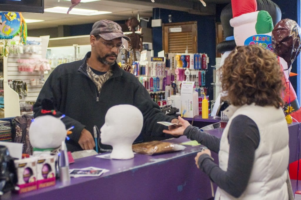 """MARCUS PONDEXTER, who has been working at Economy Party Supplies and Costumes for 16 years, said that the full-time employees at the store are """"really close."""" The store is preparing to  close on Saturday, Dec. 24 after being open for 28 years. (Photo: Drew Costley/News-Press)"""