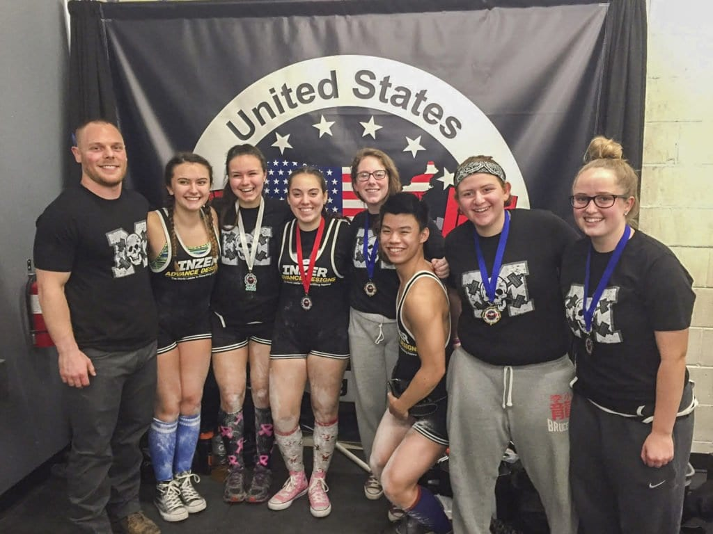 Head coach Ryan Wood, Hannah Kubisch, Emma Knoke, Christina Hall, Cassidy Bennett, Andrew Tran, Maya El-Hage and Claire Sparrowgrove pose for a photo during the 2016 Holiday Classic Powerlifting Meet in Haymarket. (Photo: Courtesy of Shannon Wood)