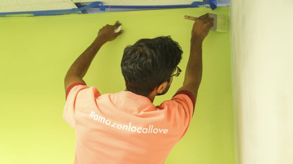 AN AMAZON VOLUNTEER PAINTS one of the walls at Homestretch during the e-commerce and cloud computing company's Local Love day at the Falls Church-based nonprofit. The Local Love program renovated the employment center, remodeled the multipurpose room and created a new health and wellness center at Homestretch. (Courtesy Photo)