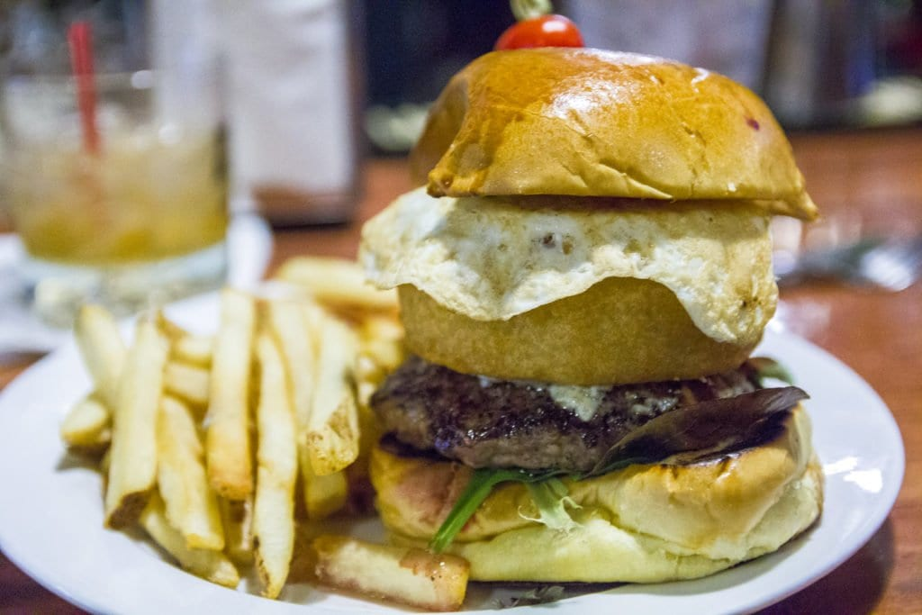 ONE OF TOWNSHEND BAR's giant new burgers is topped with grilled onions, blue cheese, an onion ring and an over-easy egg. (Photo: Jody Fellows)