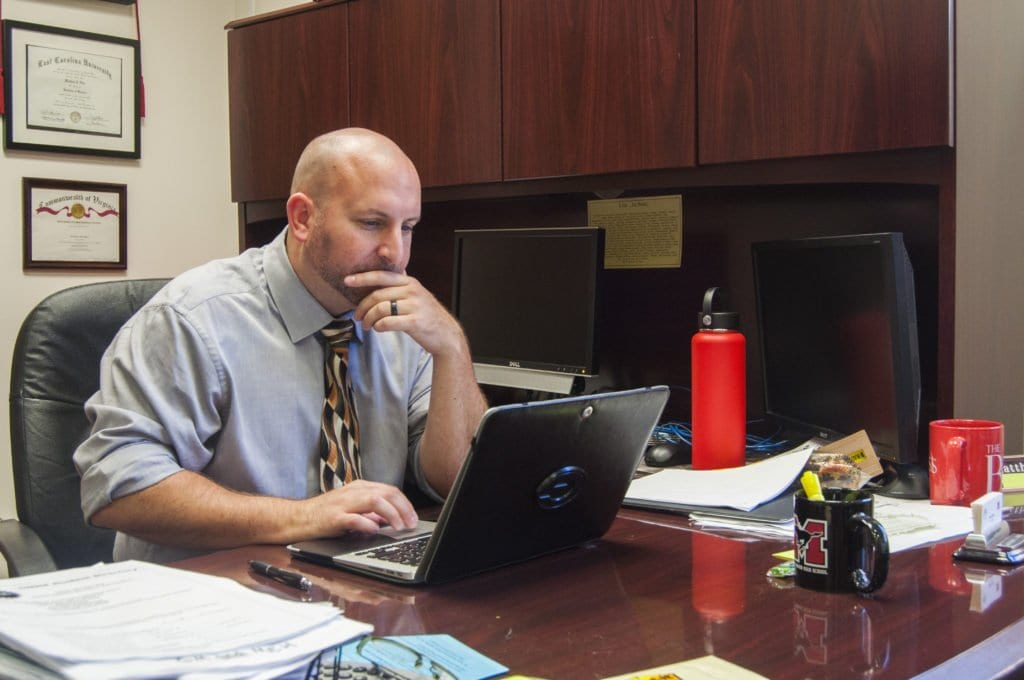 MASON'S NEW PRINCIPAL MATT HILLS checks a few emails before heading back to a staff meeting. He said that he knew that it would be a difficult transition going from being the school's assistant principal to being the principal. (Photo: Drew Costley/News-Press)