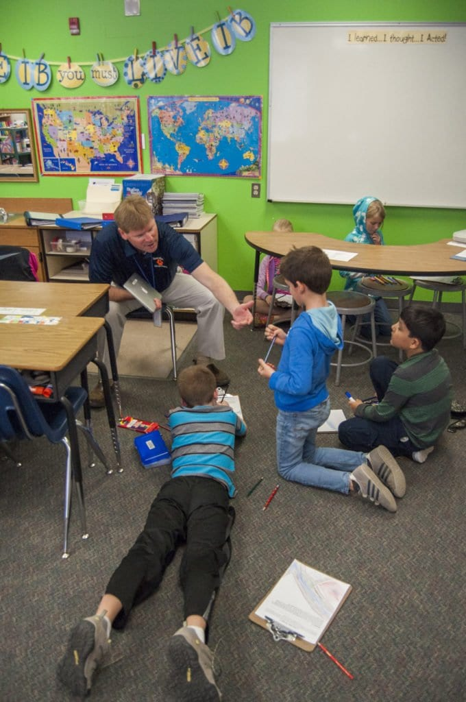 PAUL SWANSON reaches out to a student in Lacey Gandy's fourth grade class at TJ. He tested the students' knowledge of the presidents while visiting the class. (Photo: Drew Costley/News-Press)