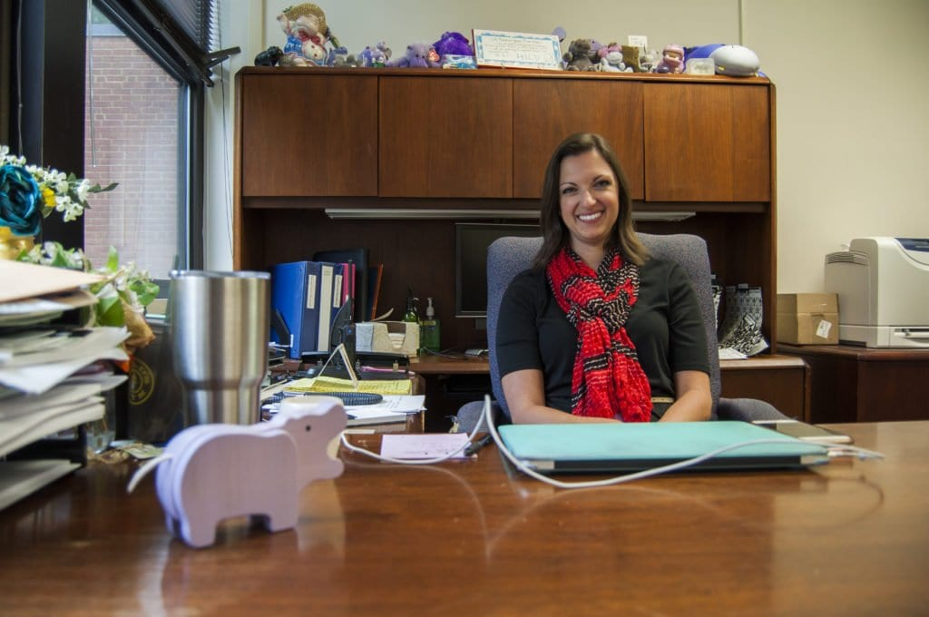 NEW MT. DANIEL SCHOOL PRINCIPAL Erin Kelly sits at the desk that was occupied by her predecessor, Kathy Halayko, for nearly two decades. Kelly said that Halayko left behind her collection of  purple hippopotami, some of which were left behind by Halayko's predecessor. (Photo: Drew Costley/News-Press)