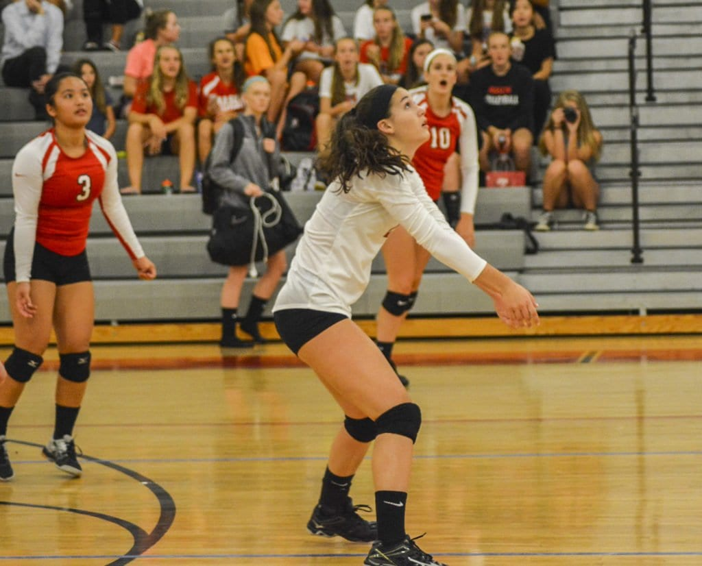 SENIOR SHAUN RODOCK GETS READY to return a hit during an early season victory for the Mustangs while her fellow seniors, Dre Dilao (left) and Kate Karstens (right) watch. Rodock stood out on the defensive side in the Mustangs defeat of Clarke County. (Photo: Carol Sly)