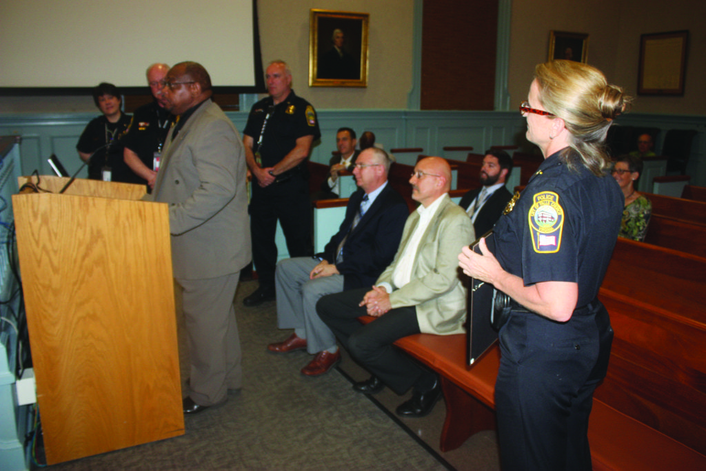 DEREK MAY, PROJECT MANAGER for Virginia's Department of Criminal Justice Services, hailed the accreditation standards that the Falls Church Police Department attained before the F.C. City Council this Monday. At the far right is Police Chief Mary Gavin. (Photo: News-Press)