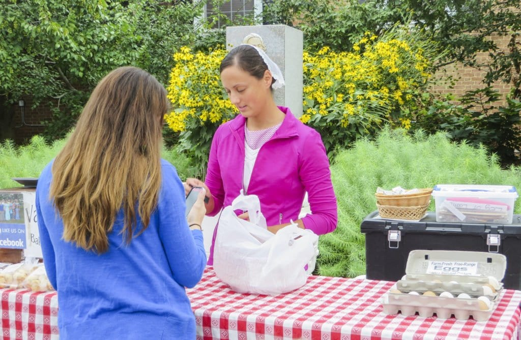 VERONICA MILLER OF VALENTINE'S Country Bakery and Meats helps a customer at the Falls Church Farmers Market, where Valentine's have been selling their goods for close to seven years. (Photo: Patricia Leslie/News-Press)