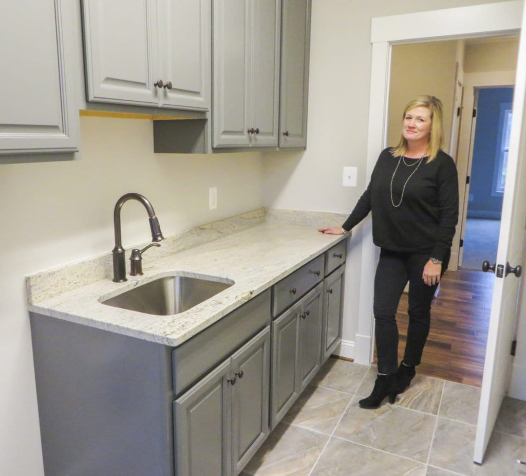 NEW DIMENSIONS PRESIDENT JENNIFER LANDERS shows off a stone countertop in one of the company's custom homes. Real estate agent Bethany Ellis, who works primarily in Falls Church, said that synthetic countertops made out of tile, stone or granite are popular among home buyers. (Photo: Patricia Leslie/News-Press )