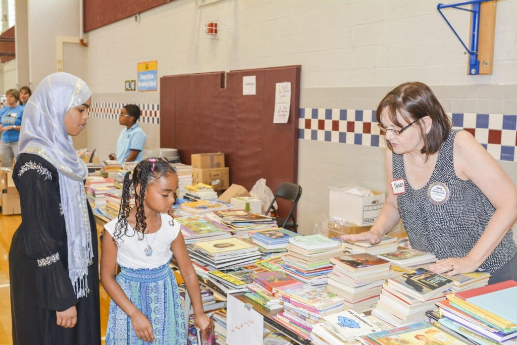Bailey's Crossroads Rotary Club past-president Susan Lydick distributes books to students at the Stuart Resource Fair, which was held at J.E.B. Stuart High School on August 9. The chapter of Rotary Club International donated $2,000 to the fair and nearly 30 volunteers gathered prior to the event to package more than 3,000 school supply kits for the fair. Several members of the club volunteered at the Stuart Resource Fair. (Photo: Courtesy of David Borowski)