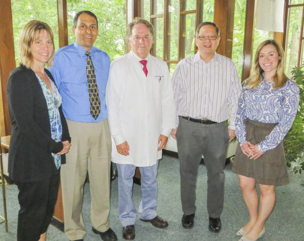 STANDING INSIDE OF THE FALLS CHURCH MEDICAL CENTER, Falls Church Medical Center staff (l to r) Kristin Vidwans, Neil Vidwans, Iver Kasenetz, Adrian Uy and Pamela Kasenetz pose for a photo. After 69 years of serving patients in Northern Virginia, the Falls Church Medical Center is closing. Everyone in the photo above except for Iver Kasenetz is moving are moving to Arlington to open Arlington Medical Associates, which will be located in Arlington's Shirlington neighborhood. (Photo: Patricia Leslie/News-Press)