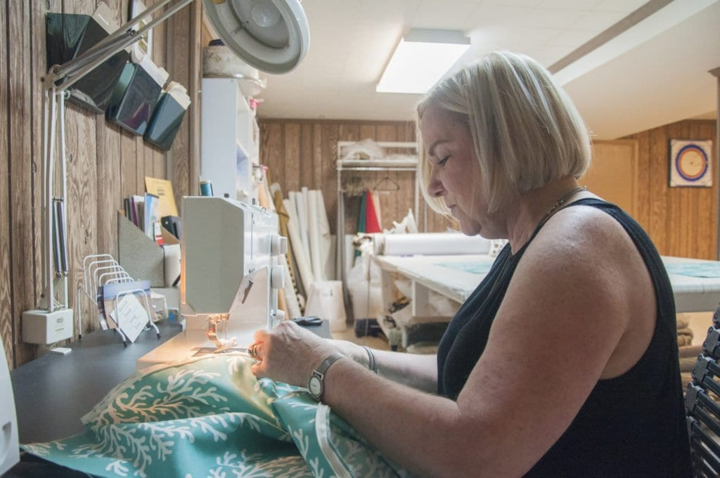 """FALLS CHURCH-BASED SEAMSTRESS CAROL SANDERS sews in her workroom at her house on Crofton Place. Her new line of pillows have been featured in the Fox TV show """"Home Free."""" (Photo: Drew Costley/News-Press)"""