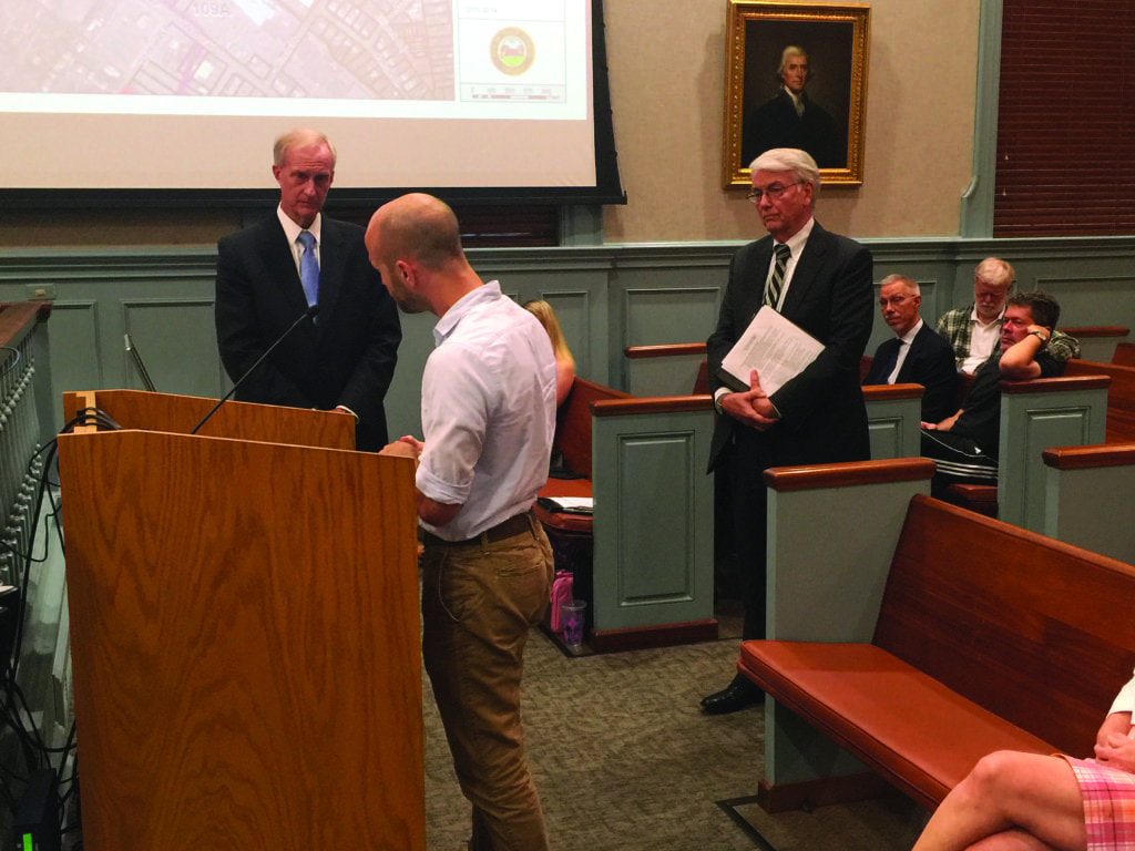FALLS CHURCH CITIZEN Richard Rabil (at podium) assailed the sudden shutdown of two Metro bus lines on Rt. 7 through Falls Church Monday night to the F.C. City Council and to WMATA board chair Jack Evans (to his right). (Photo: News-Press)