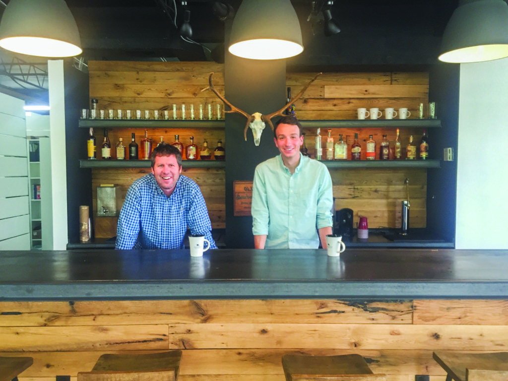 Greenspur's owner/founder Mark Turner and the company's director of design Zach Gasper stand behind the bar in the company's office on W. Broad Street. Gasper said that the company seeing projects through from start to finish is a benefit to their clients. (Photo: Courtesy of Brooke Clime)