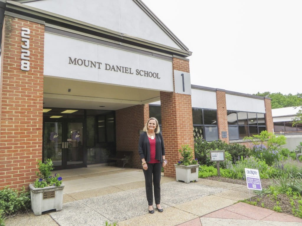 """Halayko stands outside of the Mount Daniel School, where she has worked for 28 years, serving as the school's principal for the last 18 years. Halayko is retiring from the school on June 30. She said that she was """"amazed"""" to be selected as this year's Grand Marshal in an interview with the News-Press. (Photo: Patricia Leslie/News-Press)"""