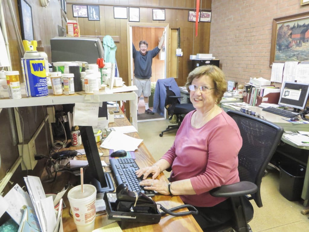 Diane Flood (right), one of the owners of Falls Church Florist, sits at the desk in the store's office as Mike Flood stands joyfully in the background. Mike Flood began helping his uncle and aunt around the shop when he was eight years old. (Photo: Patricia Leslie/News-Press)