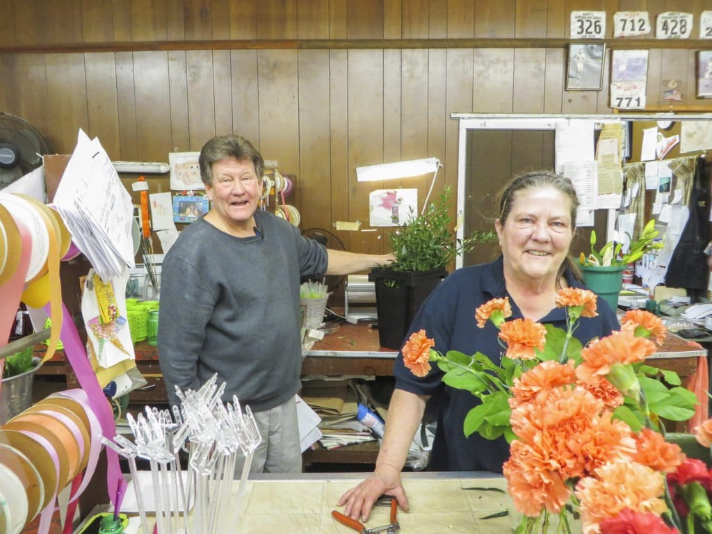 """Mike Flood (left), one of the owners of Falls Church Florist, stands behind the counter at the floral shop with designer Katherine Gamble. The local floral shop is closing at the end of June after being open and serving the Falls Church community for 66 years. Flood told the News-Press that the floral business has changed """"180 degrees"""" over the past 35 years, due to franchise and Internet floral businesses. The store is having two big parking lot sales on Sunday, May 22 and Sunday, June 12 from 9 a.m. – 5 p.m. (Photo: Patricia Leslie/News-Press)"""