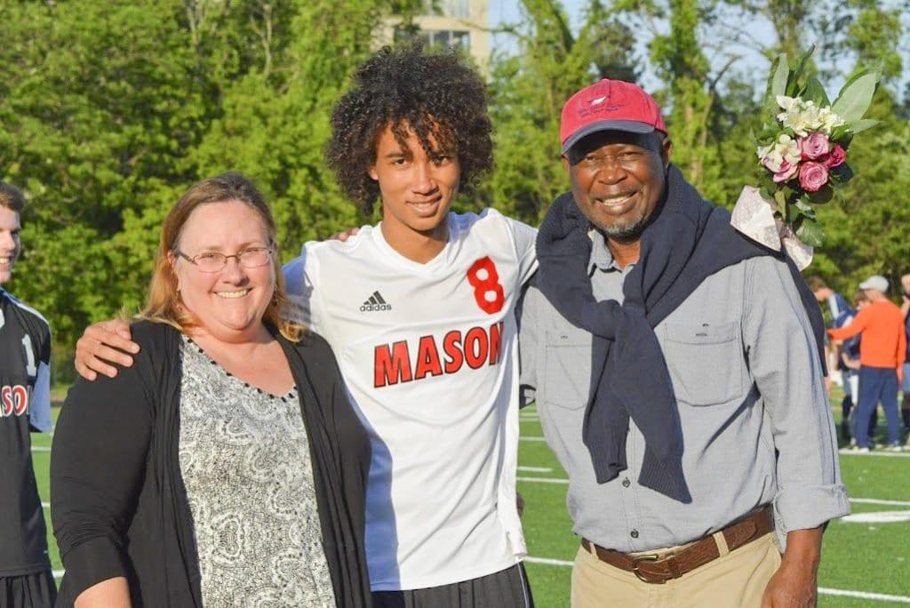Mason senior Samsu Sallah stands with his parents during the soccer team's senior night celebration. (Photo: Carol Sly)
