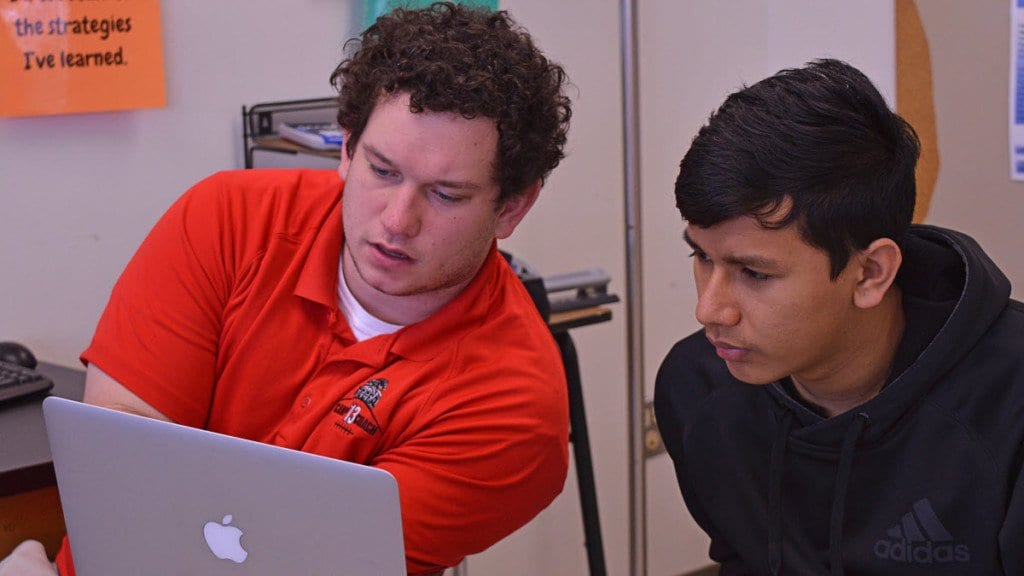 Senior Bikash Shahi (right) works on an assignment with Mr. Larcamp using his school-issued Macbook. (Photo: Eric Clinton)