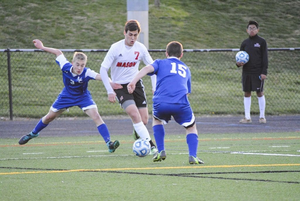 MASON SENIOR ELLIOT MERCADO dribbles the ball between two Madison County High School defenders during the Mustangs' 7-0 win over the Mountaineers. Mercado scored a hat trick and assisted with another in the Mustangs' 8-0 win over Central High School. (Photo: Carol Sly)