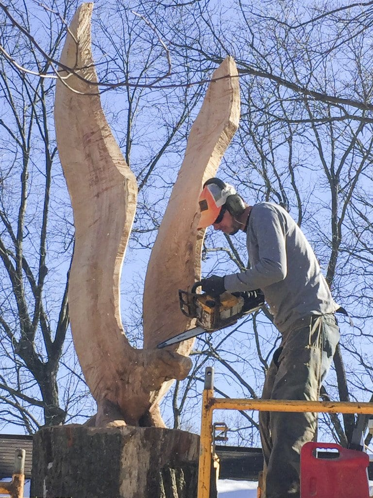 Chainsaw carver Andrew Mallon works on a sculpture of an eagle in Falls Church. (Photo: Courtesy of Andrew Mallon)