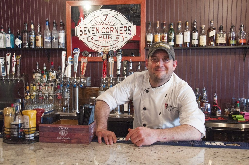 RYAN COOLEY, general manager and executive chef of Seven Corners Pub, stands behind the restaurant's bar, where he sometimes serves as a bartender. Formerly Public House No. 7, the restaurant has undergone a transformation over the past year and is now attempting to win back the trust of the Falls Church community. (Photo: Drew Costley/News-Press)