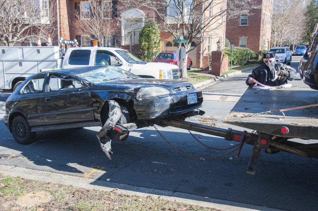 A Falls Church City police officer fills out paper work while the Honda Civic, one of the cars damaged in today's accident, is loaded onto a tow truck. (Photo: Drew Costley/News-Press)