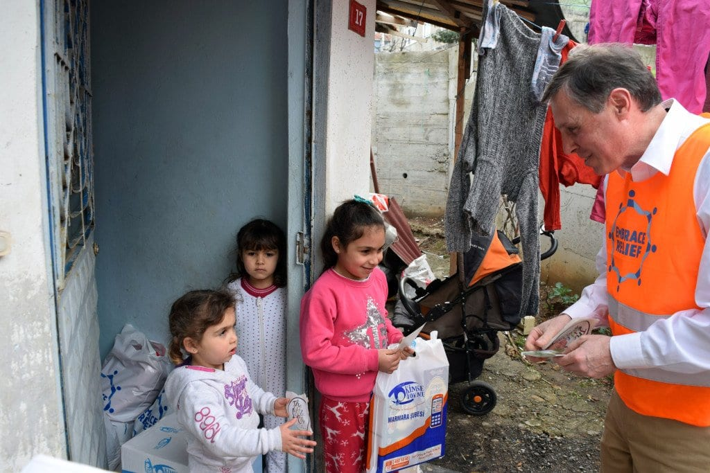 FALLS CHURCH MAYOR David Tarter (right) is shown in Istanbul, Turkey presenting coats and blankets to child refugees earlier this month. Tarter was part of a delegation of the Northern Virginia Regional Commission, whose participating jurisdictions collected the vital aid to the countless Syrian refugees who have fled to Turkey. (See News Briefs, page 9). (Photo: News-Press)