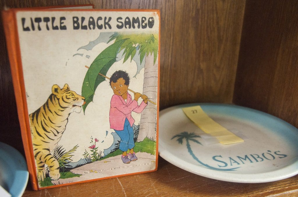 """""""Little Black Sambo,"""" the first book by writer Helen Bannerman and one of two Sambo's plates that are for sale in Quinn Auction Galleries' Howard Wolverton Collection sale sit on a shelf in the gallery. (Photo: Drew Costley/News-Press)"""