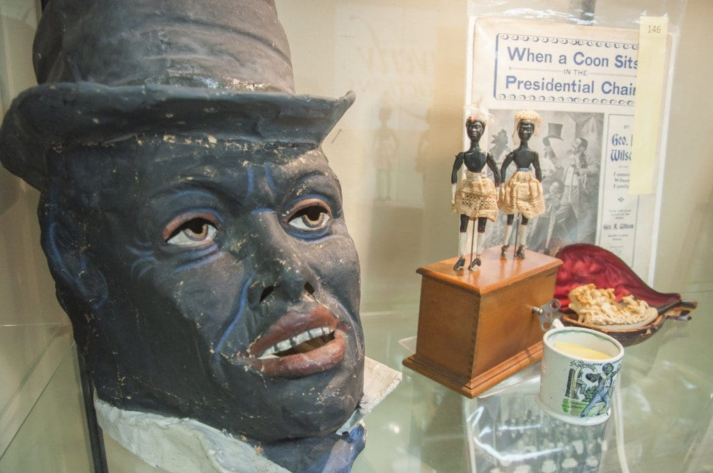 An antique papier-mache Mardi Gras minstrel mask and other items on the auction block at Quinn's on Thursday sit in a case at the local gallery. (Photo: Drew Costley/News-Press)