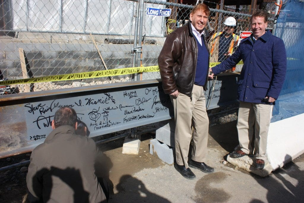WHILE AN UNIDENTIFIED person adds her signature to the many already written on the beam that subsequently topped off the Kensington building, to the right Kensington's Harley Cook and partner Ed Novak of Nova-Habitat enjoyed the moment. (Photo: News-Press)