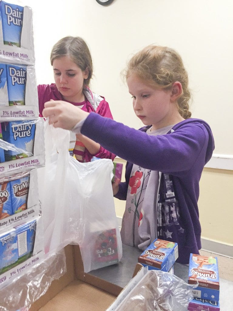 Falls Church City Girls Book Club members Fiona Scheer and Julia Mineo bag food at the Arlington Food Assistance Center. (Photo: Courtesy of Jessica Morris)