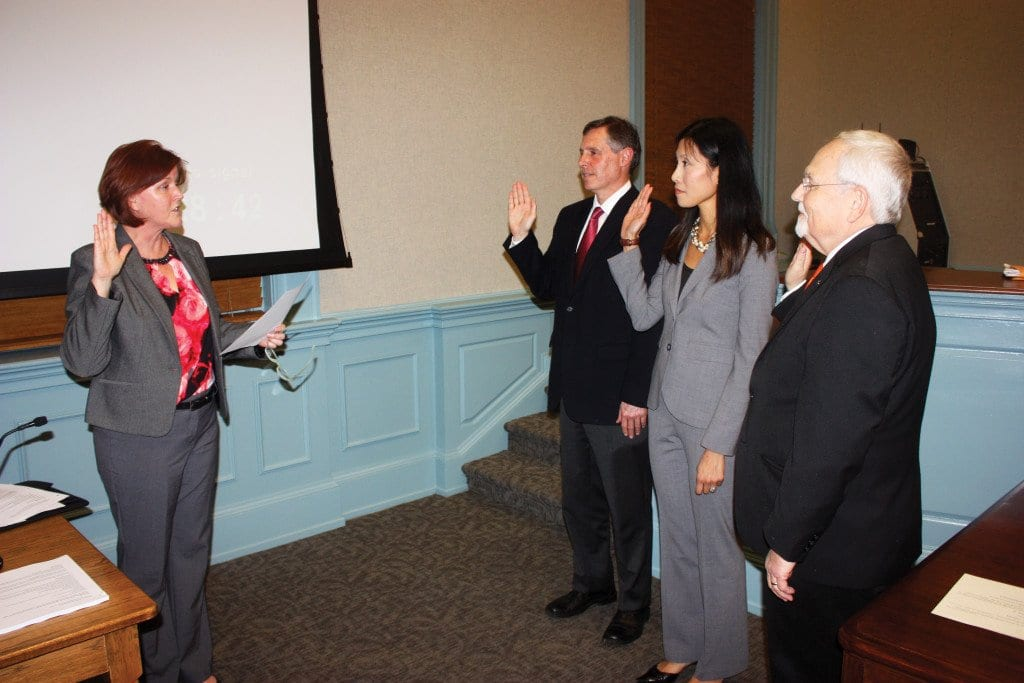 FALLS CHURCH CITY Clerk Celeste Heath (left) swore in three members to new four year terms on the Falls Church City Council Monday night, including (l. to r.) incumbent Mayor David Tarter, new electee Letty Hardi and incumbent Councilman Phil Duncan. The three will commence their new terms as of Jan. 1 after winning the election last month. (Photo: News-Press)