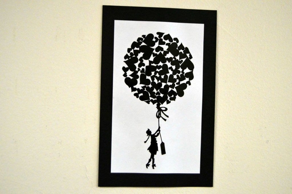 Piece of Contrasto artwork above displaying a little girl with many hearts clumped together to make up a balloon. The piece of the artwork is by freshmen Sarah Valley.