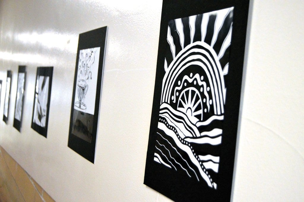 A variety of pieces of Contrasto artwork pasted on the ramp hallway near the auditorium. These projects were assigned for art classes 1-4.