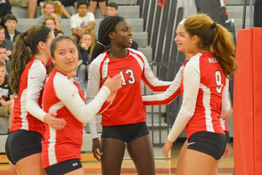The mustangs gather around senior Vicky-Marie Addo-Ashong after scoring a point during their victory over Madison County High School on Tuesday. (Photo: Carol Sly)