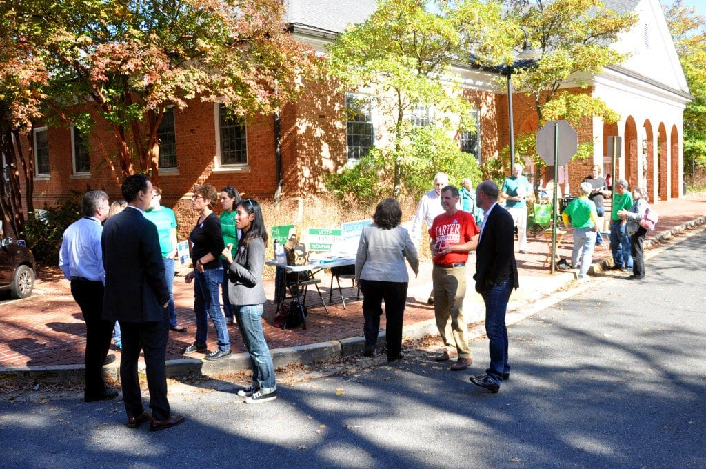 OUTSIDE THE POLLING place in the Falls Church Community Center on election day Tuesday, two of the winning candidates for City Council – Mayor David Tarter and Letty Hardi – are shown campaigning amid a busy scene of other volunteers and prospective voters. (Photo: News-Press)