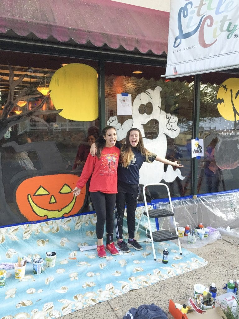 GHOST BRUSHERS Alex Dunie (right) and Rebecca Horovitz take a short break after painting their Halloween window creations outside Argia's Italian Restaurant. (Photo: Courtesy of Bruce Horovitz)