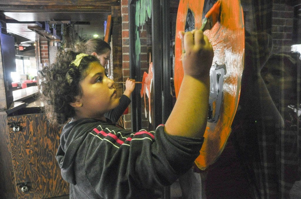 FALLS CHURCH RESIDENT ANNIKA NICHEN paints a jack-o-lantern on one of the windows of Ireland's Four Provinces on Saturday, Oct. 17, the last official day of the 8th Annual Halloween Store Window Painting project. (Photo: Drew Costley/News-Press)
