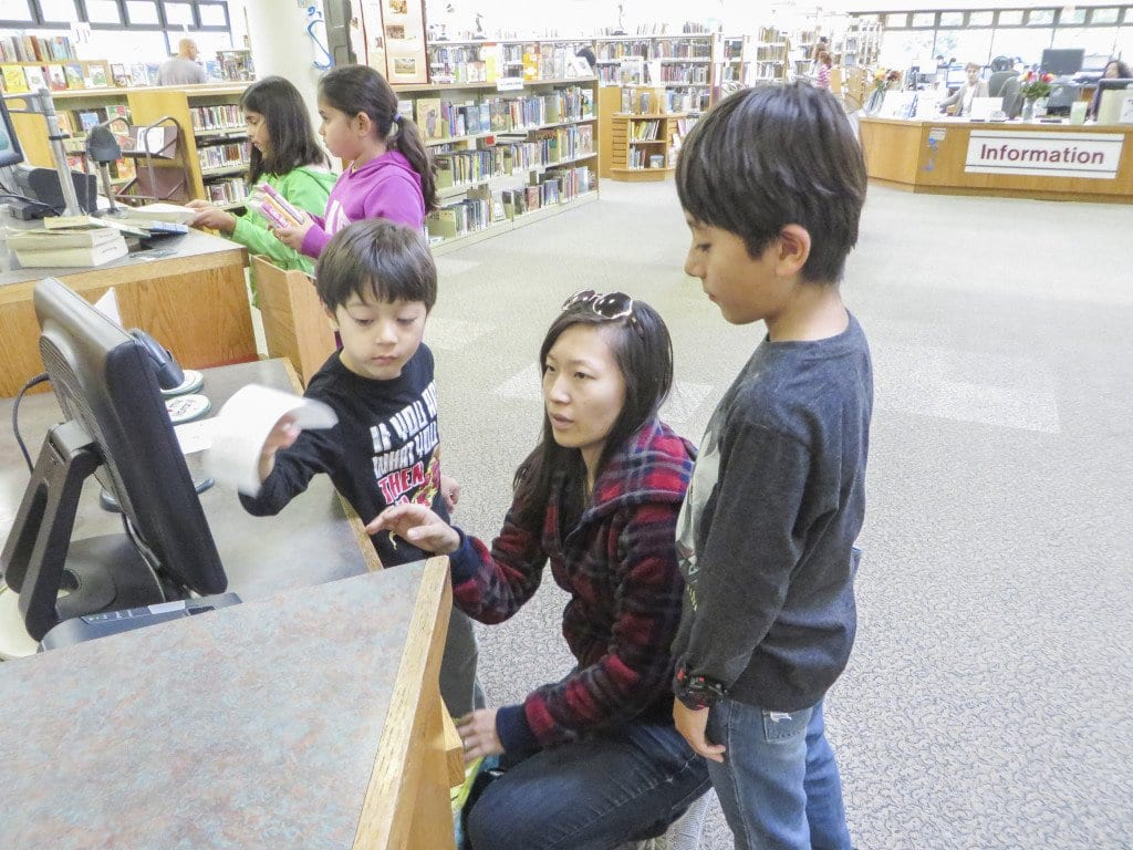 Chiharu Abdin (center) and her sons Ali (left) and Malek check out their library receipt at the Tysons-Pimmit Regional Library on Saturday. (Photo: Patricia Leslie/News-Press)