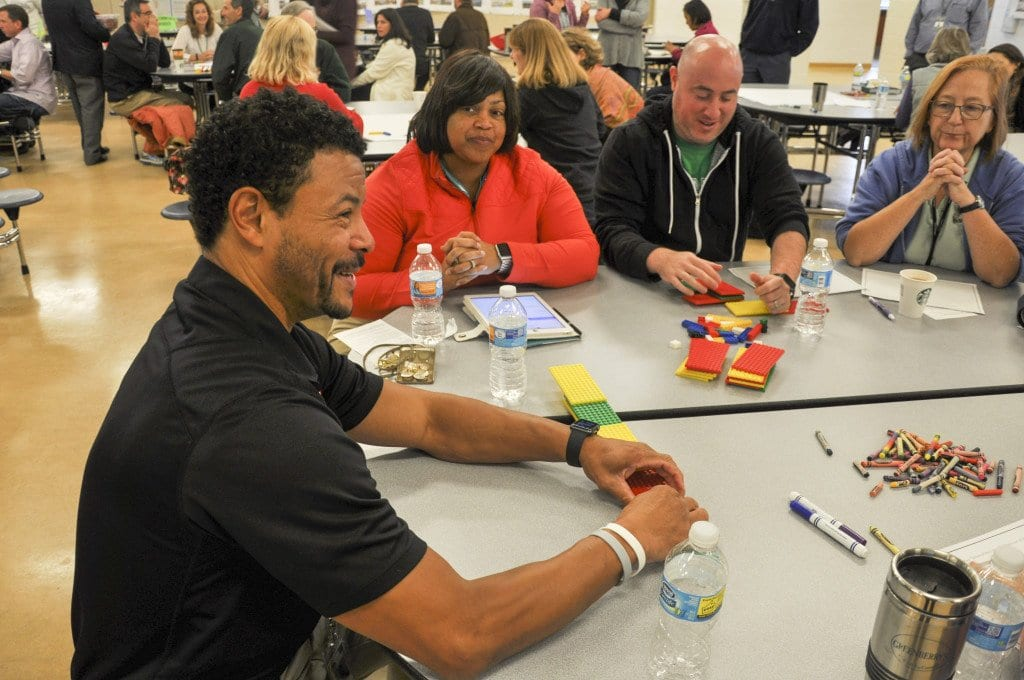 George Mason High School principal Tyrone Byrd gets ready to build a structure with Lego blocks during one of the exercises at Saturday's forum. (Photo: Drew Costley/News-Press)