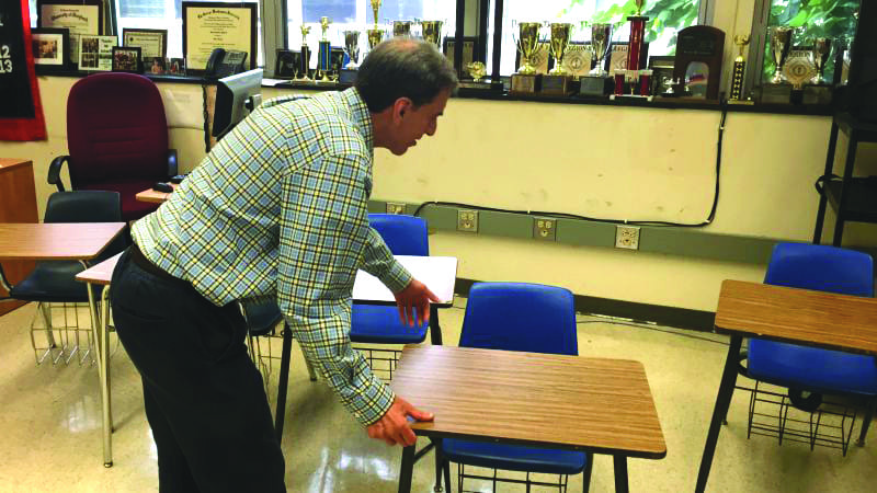 "Theory of Knowledge teacher Mr. Scharff moves desks to accommodate the next class. Mr. Scharff has had to move the desks at the end of every block 3 class because of the difference in size between his classes. ""One difficulty is that theory of knowledge was designed to be a seminar and having class discussions becomes difficult,"" said Mr. Scharff. (Photo: Dorian Charpentier)"