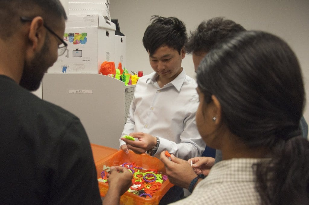 Zhao shows his fellow students some of the products of the school's 3D printers.  (Photo: Drew Costley/News-Press)