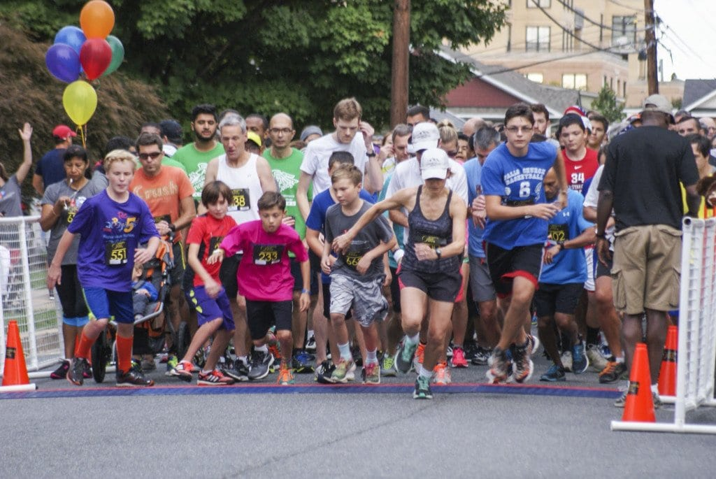 Jim Sherwood (center, white shirt, fixing earbud) and the rest of the runners take off from the starting line at the Falls Church Education Foundation's Run for the Schools on Sunday. (Photo: Carol Sly)