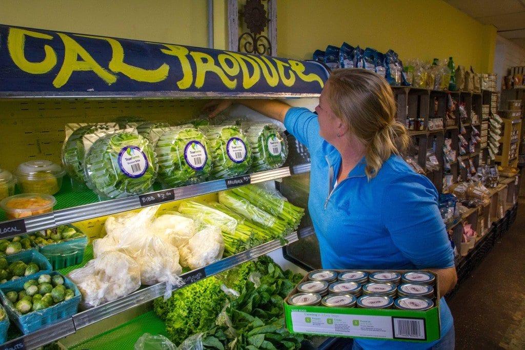 Tamara Powell adjust the lettuce display at The Local Market. (Photo: Jody Fellows)