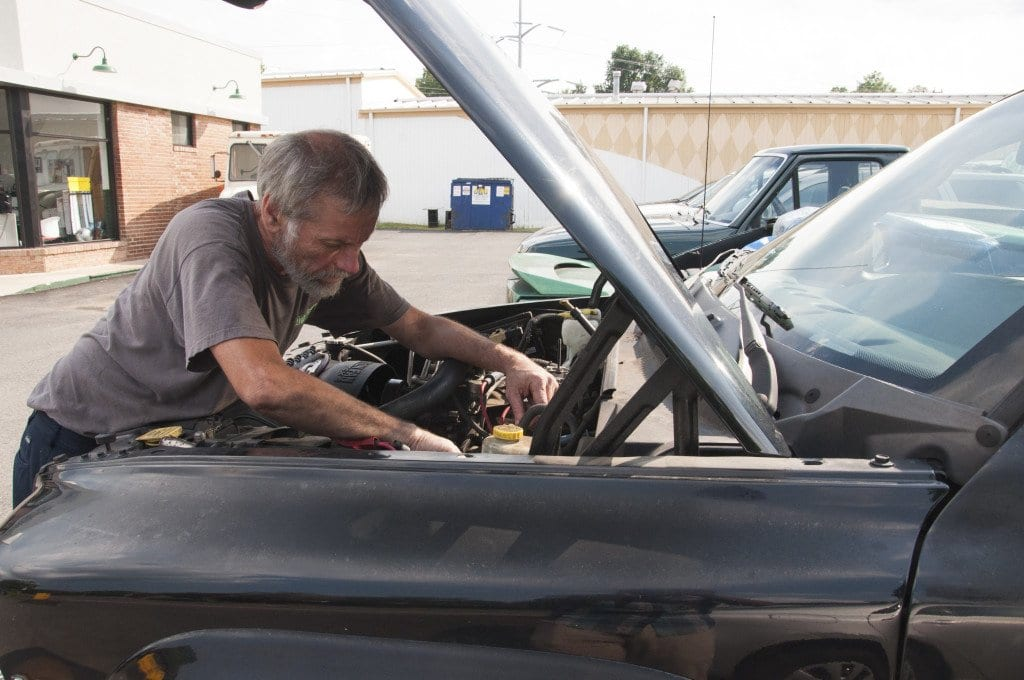 Chris Offner of Smokey's Garage drills broken spark plugs out of a Dodge Dakota. He said that mechanics have to buy more equipment to test technologically-advanced cars and stay on top of how to use it. (Photo: Drew Costley/ News-Press)