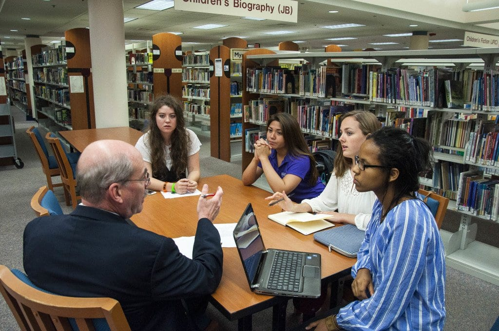 J.E.B. Stuart High School students (l to r) Cassie Marcotty, Abby Conde, Anna Rowan and Lidia Amanuel meet with Jim Kilbourne, president of the Lake Barcroft Association, at George Mason Regional Library in Annandale on Tuesday night about the effort to rename the school. (Photo: Drew Costley)