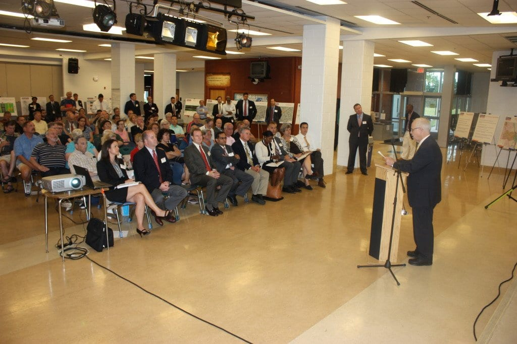 FALLS CHURCH VICE MAYOR David Snyder (at podium) welcomed a large audience, only half of which is shown in this photo, to Falls Church's Henderson Middle School Tuesday for an information session on plans for the makeover of Interstate 66 inside the beltway. (Photo: News-Press)