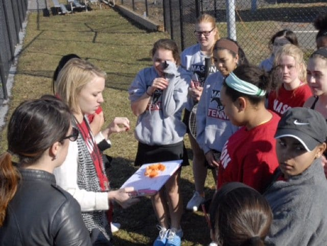 Members of the girls varsity tennis team gather around Ware for a few announcements before a match. Last season, the team made it all the way to states, before getting eliminated in the second round. (Photo: Courtesy of Anna Connole)